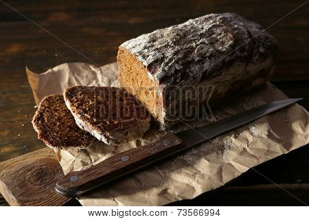 Sliced rye bread and knife on craft paper on cutting board on wooden background