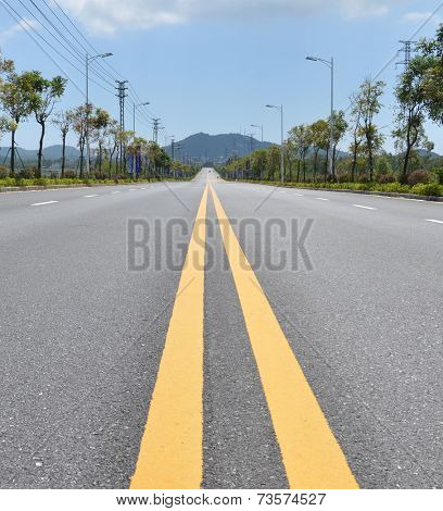 a two lane road with a blue sky