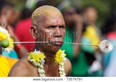 BATU CAVES, MALAYSIA, FEBRUARY 07, 2012: Hindu devotee with pierced cheeks in annual Thaipusam religious festival in Batu Caves, near Kuala Lumpur, Malaysia