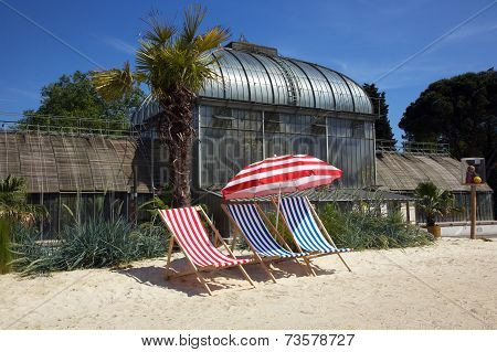 Striped Deckchairs And Umbrella On A Sand