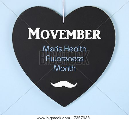 Movember Fundraising For Mens Health Awareness Charity Message On Black Heart Shape Blackboard On Bl