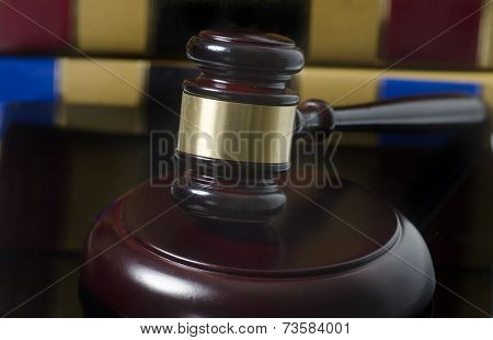 Gavel on wood block with legal books in background