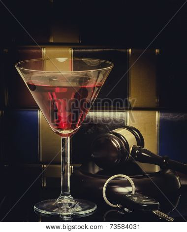 Drink driving law legal concept image - car keys - wine glass and gavel with legal books in background,