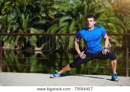 Beautiful male runner stretching before workout, fit man doing stretching exercises outdoors