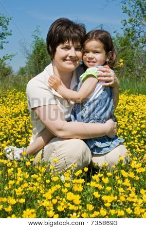 Mother And Her Daughter Sitting Among Yellow Flowers