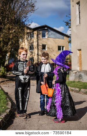 Three adorable trick or treaters begging for Halloween candy