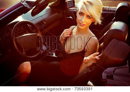 blonde girl in cabriolet car sunny day at the city