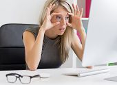 image of annoying  - Tired woman barely keeps her eyes open in front of computer - JPG