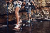picture of dam  - Cropped image of a hiking woman and man crossing a dam by balancing on the rocks in the dam - JPG