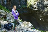 picture of cave woman  - Woman hiker standing near the entrance of a cave by a warning sign - JPG