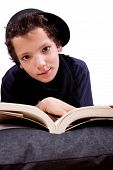 image of storytime  - boy lying on a pillow reading - JPG
