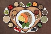 picture of ashwagandha  - Large health food selection in bowls on a heart shaped wooden board over lokta paper background - JPG