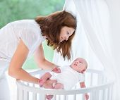 foto of bassinet  - Young Beautiful Mother Putting Her Newborn Baby Into A White Round Crib Next To A Window - JPG