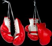 stock photo of knockout  - Two pair of red and white boxing gloves hanging and isolated on a black background - JPG