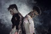 pic of zombie  - Two male zombies back to back on black smoky background looking down and away