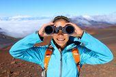stock photo of binoculars  - Hiker looking in binoculars enjoying spectacular view on mountain top above the clouds in Haleakala national park - JPG