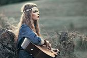 stock photo of hippy  - Beautiful hippie girl with guitar sitting on grass near stone