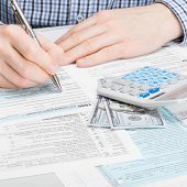 image of cpa  - Man filling out 1040 US Tax Form  - JPG