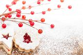 stock photo of linzer  - Christmas Linzer cookies decorated with powdered icing sugar and red decorations in the background - JPG