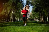 stock photo of strongman  - Athletic runner training in beautiful green park at sunny evening - JPG