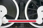 pic of train-wheel  - Black wheel of train with white and red mechanism on railway - JPG