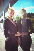 picture of blazer  - young blue eyes woman with short blonde hair in elegant  black blazer reflection in glass - JPG