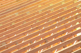 stock photo of rafters  - A roofing contractor installing rafters at a commercial residential development - JPG