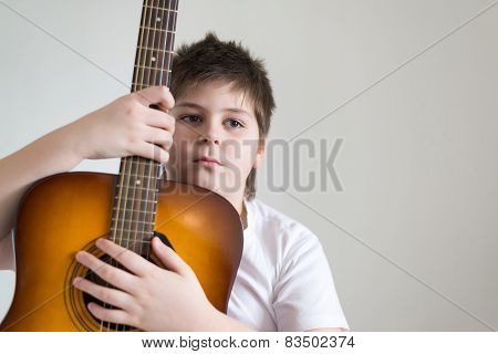 Teenage boy learning to play a guitar