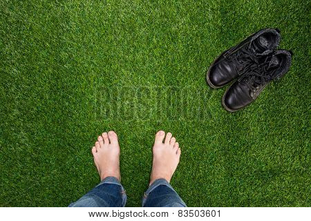 Mens Feet Resting On Green Grass With Standing Boots