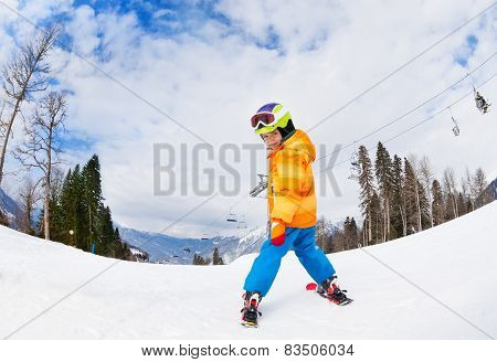 Boy wearing ski mask skiing view from back