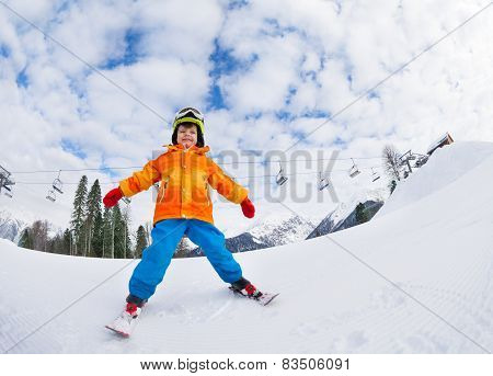 Boy with mask and helmet skiing on ski resort