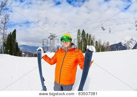 Young man in mask holds ski during mountain trip