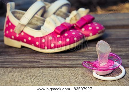 Baby shoes and a pacifier on the old wooden background. Toned image