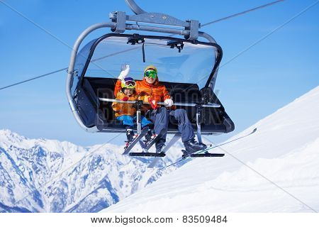 Boy and dad sit in chair lifting on the mountain