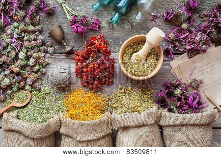 Healing Herbs In Hessian Bags, Wooden Mortar, Small Bottles On Old Wooden Table, Herbal Medicine. To
