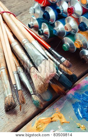 Vintage Stylized Photo Of Paintbrushes Closeup, Open Multicolor Paint Tubes And Artist Palette.