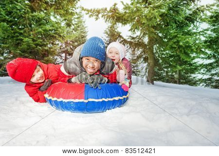 Excited girl and two boys on snow tube in winter