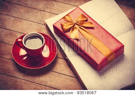Cup Of Coffee And Gift Box With Book On A Wooden Table