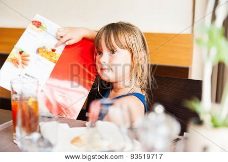 Cute little girl choosing her meal in a kid's menu in a restaurant