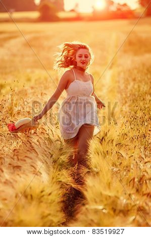 Happy Young Blonde Girl In White Dress With Straw Hat Running Through The Golden Wheat Field