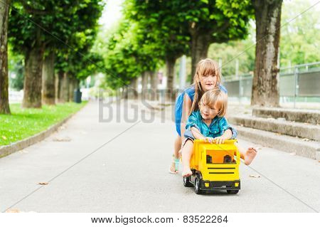 Outdoor portrait of adorable kids having fun outdoors, playing with a big toy car