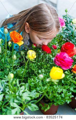 Little girl smelling flowers in flower shop