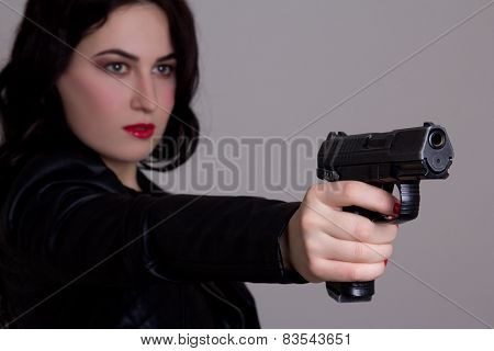 Beautiful Sexy Woman In Black Shooting With Gun Over Grey