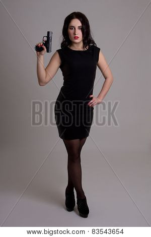 Full Length Portrait Of Sexy Woman In Black Dress With Gun Over Grey