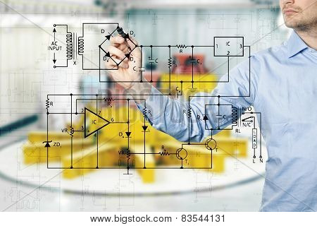 Electrical Engineer Draws A Diagram Of A Circuit. Power Plant Interior In Background