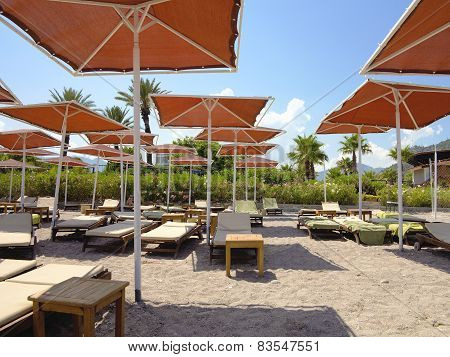 Red Umbrellas And Empty Loungers On A Sand Beach