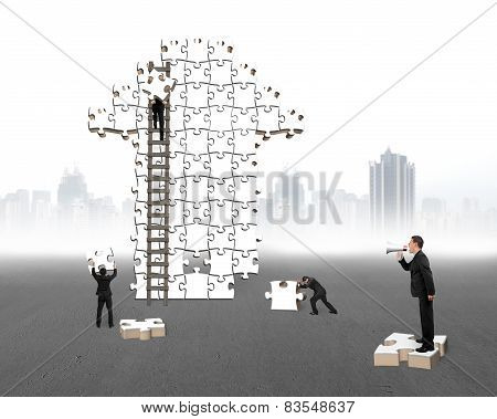 Businessman Commanding Workers To Build Arrow Jigsaw Puzzle With Cityscape