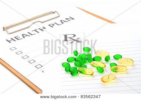 Pill Capsules Resting On Medical Health Plan Or Patient Record Form