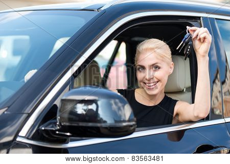 Young woman with keys sitting inside car