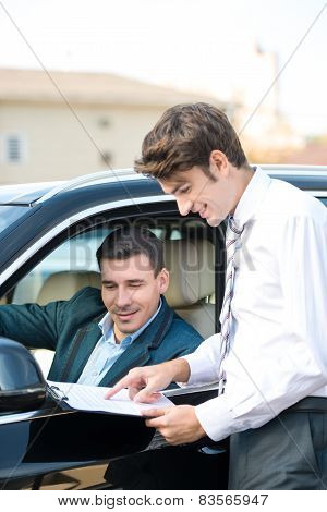 Car dealer and young man signing a contract
